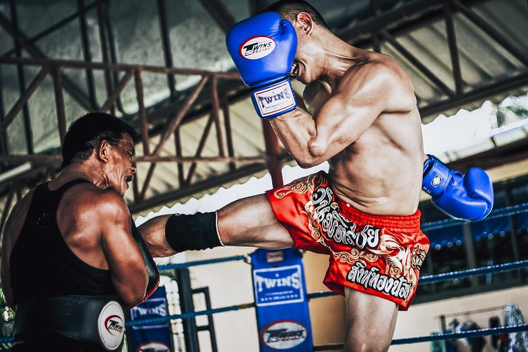 pratiquant de boxe effectuant un middle kick sur son partenaire