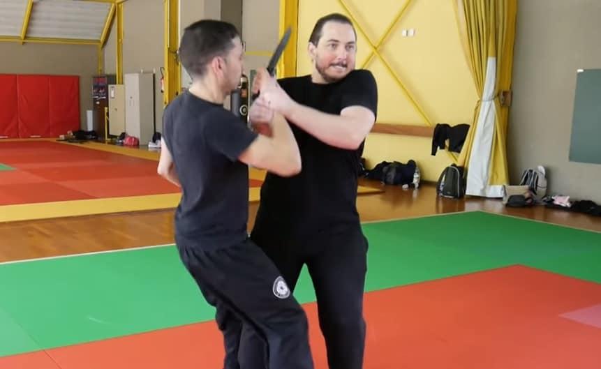 deux individus en lutte, dont l'un avec un couteau et la victime essayant d'exécuter une clé articulaire