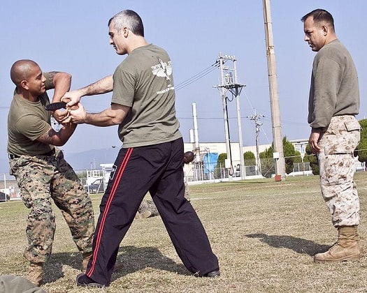 instructeur de self-défense faisant une démonstration technique de désarmement contre couteau