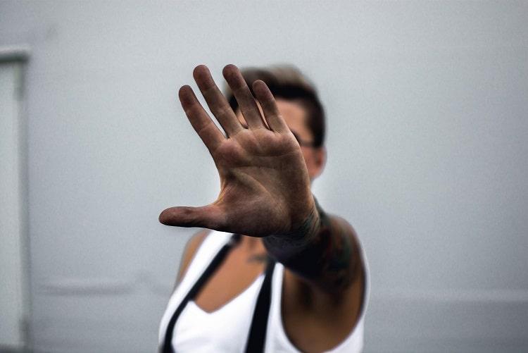 individu en extérieur, avec main ouverte devant lui en protection