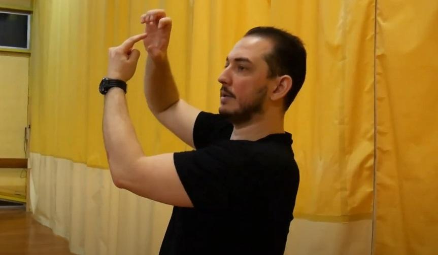 doigts repliés vers l'intérieur de la main pour représenter le point de convergence de la pression exercée sur la cuisse lors d'une bise de cheval